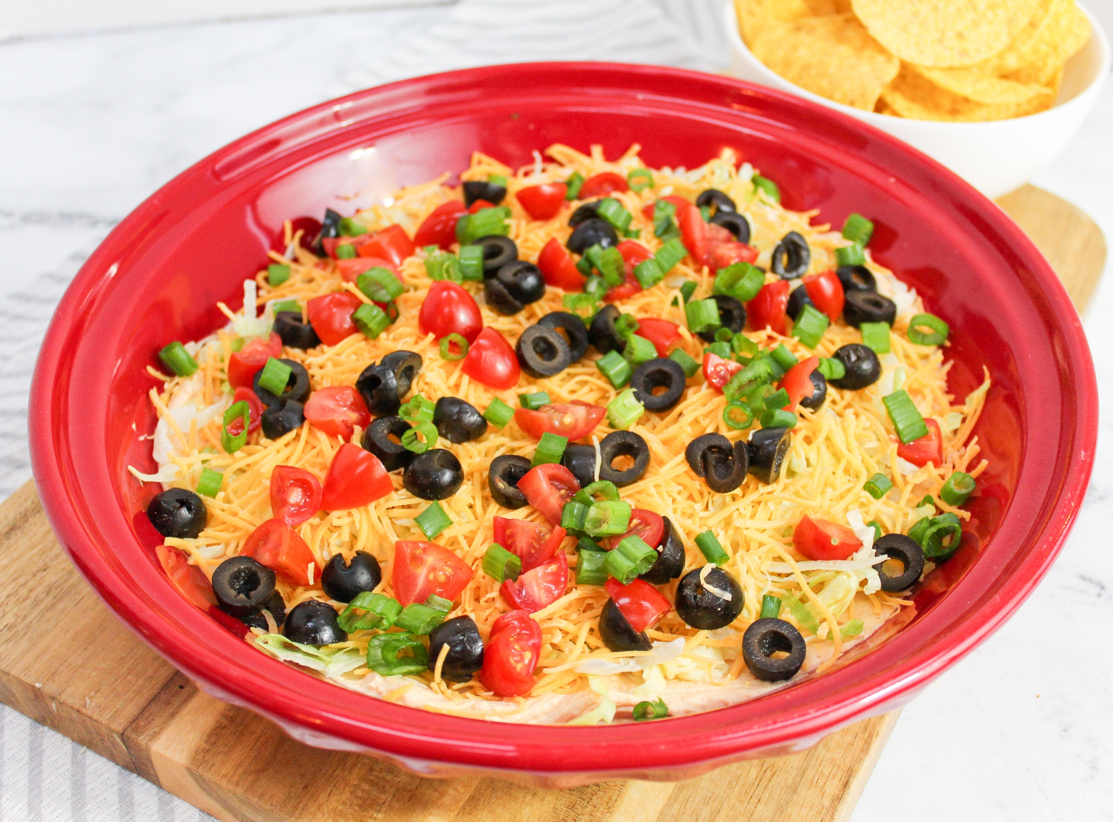 taco dip with topping in a red plate