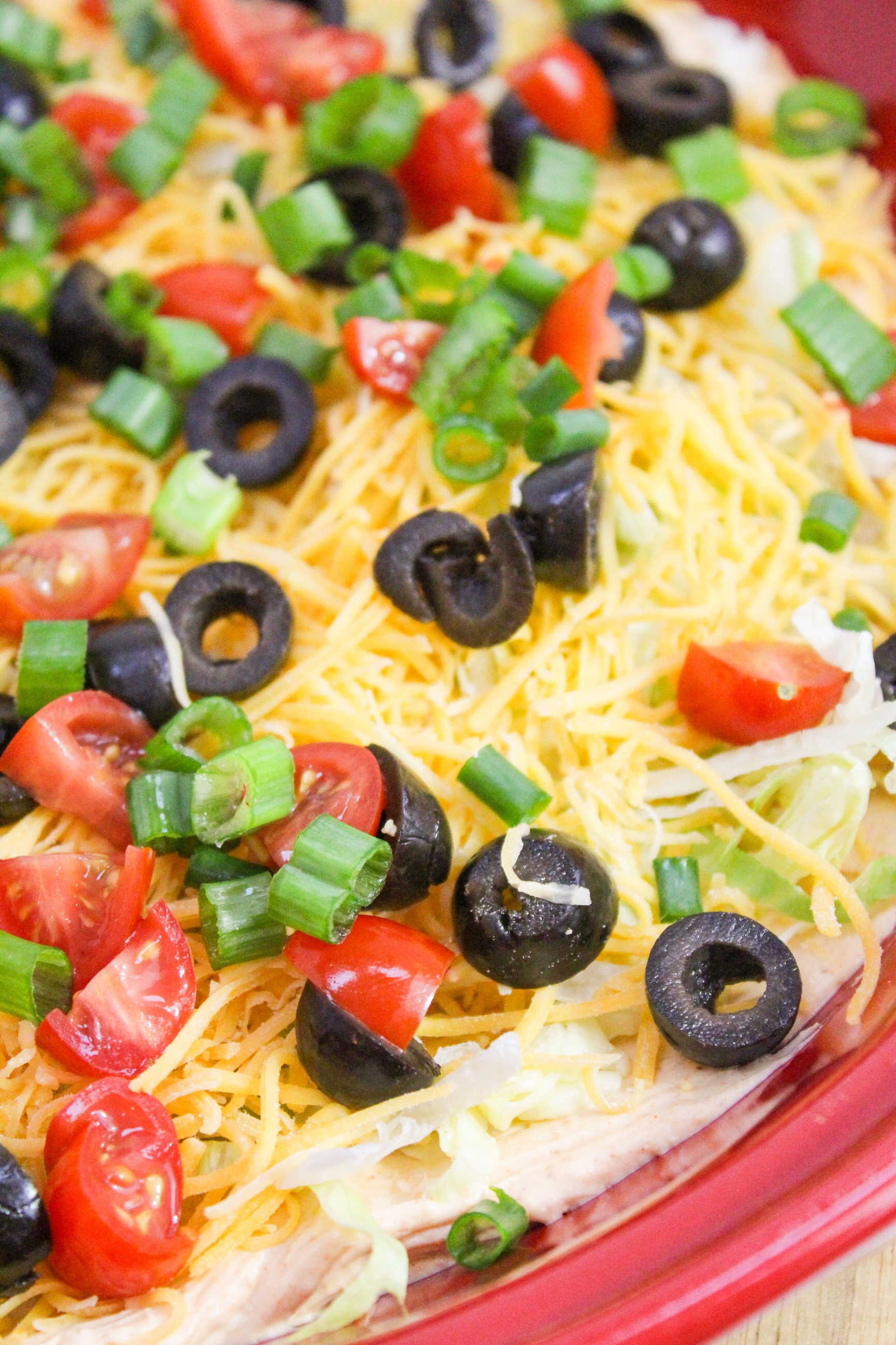 close up photo of taco dip with lettuce, tomato, olives, and onion