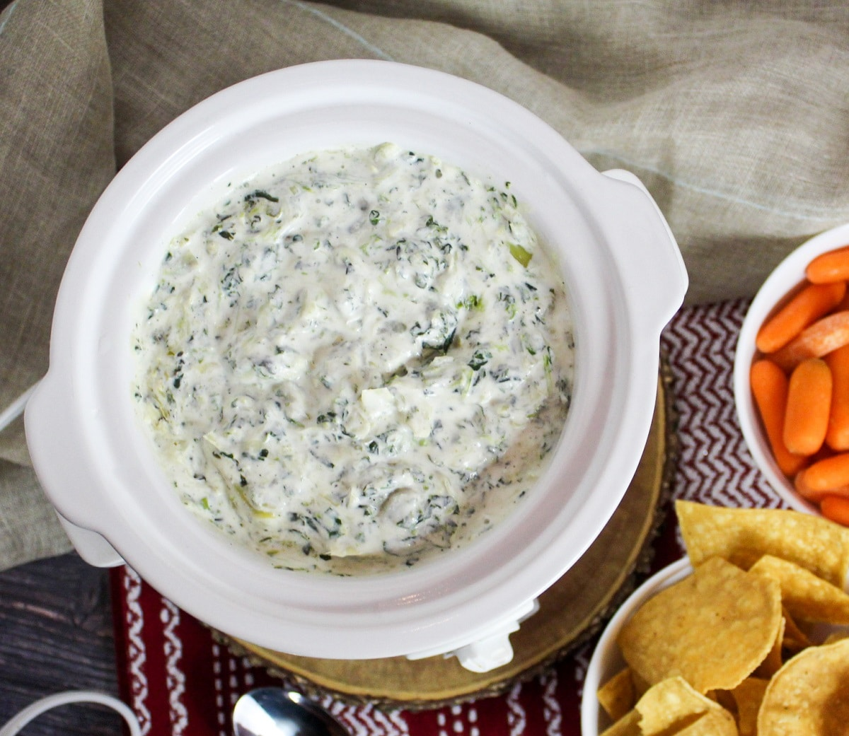 overhead picture of cheesy spinach and artichoke dip with chips and carrots