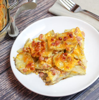 Sliced potatoes, cheese, and diced ham baked in a casserole dish