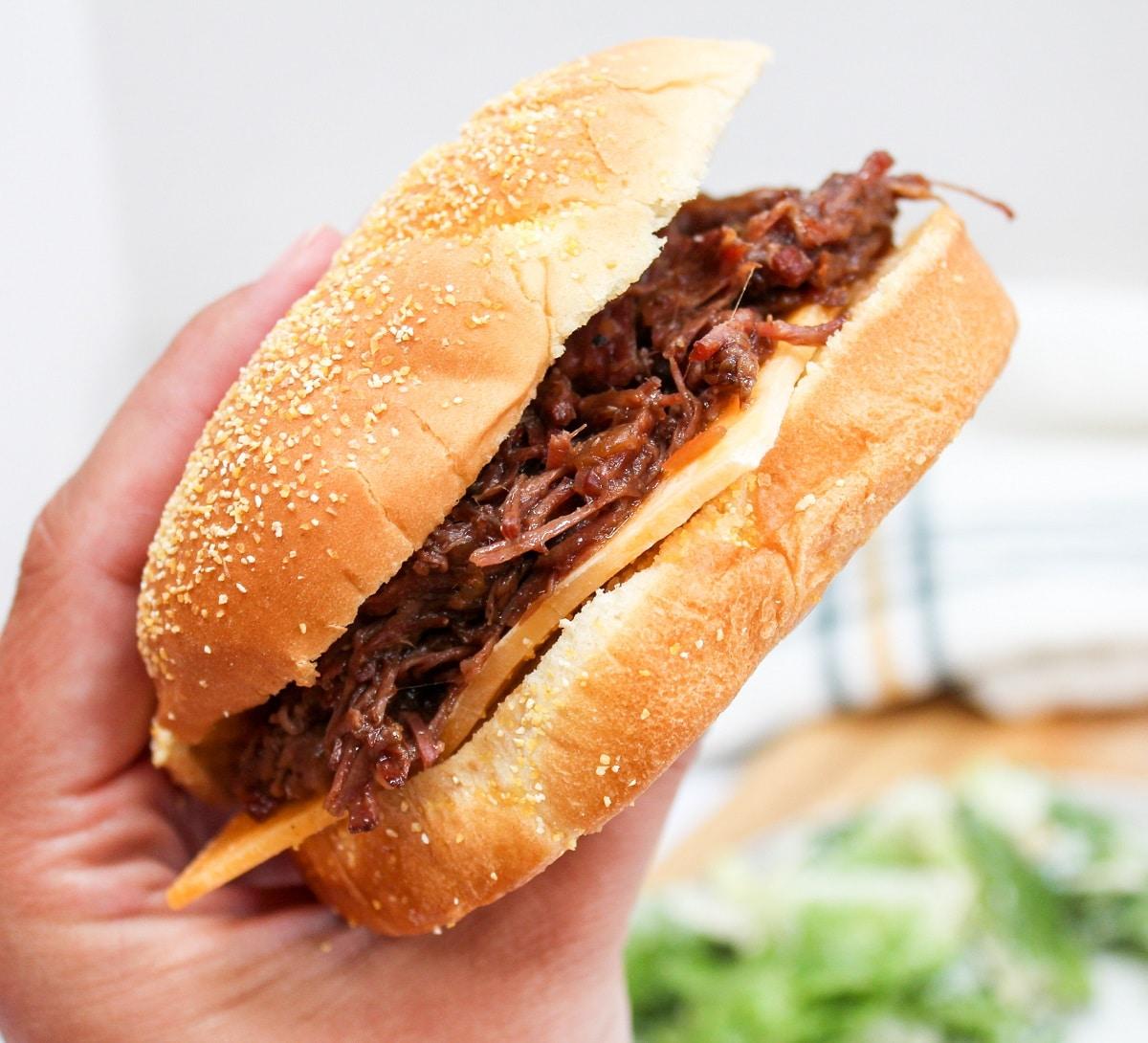 slow cooker hot beef sandwich held in hand