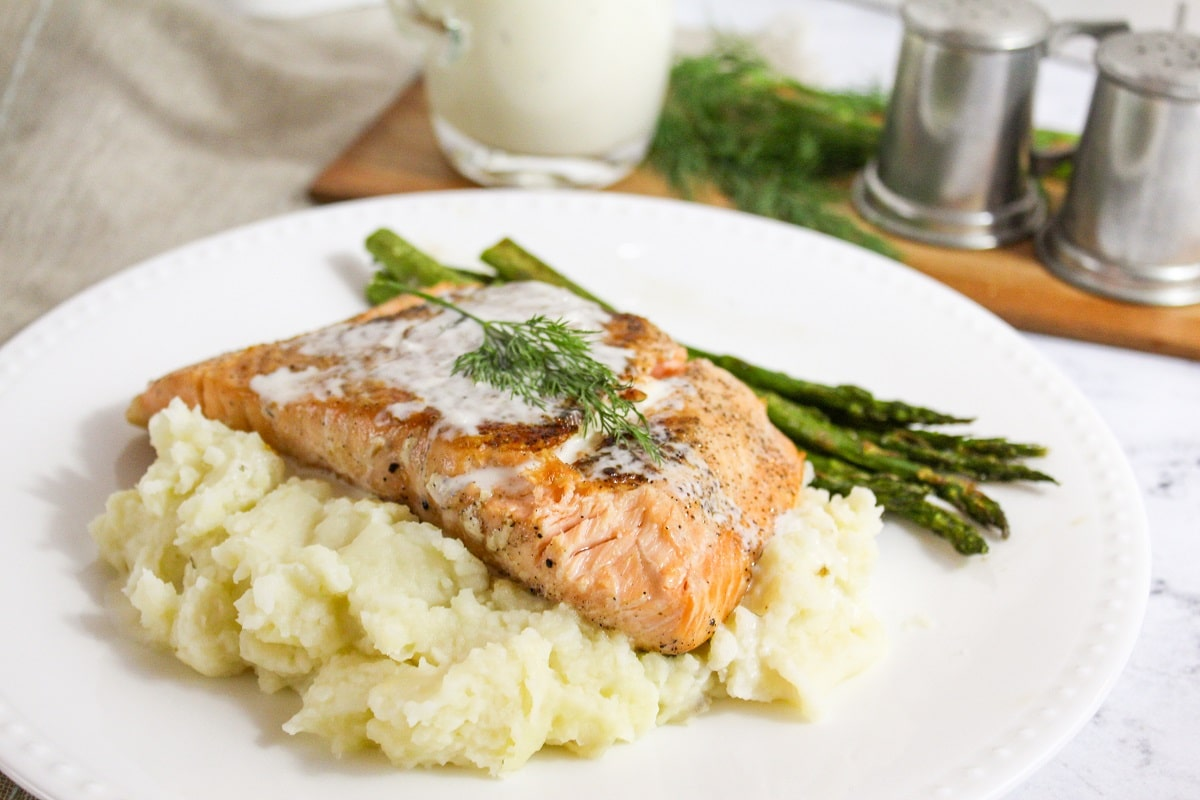 plated salmon with champagne sauce and dill on topand mashed potatoes