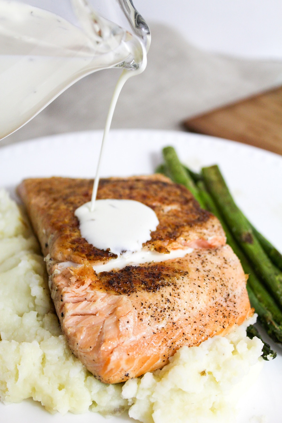 salmon with champagne sauce and dill on top poured on top