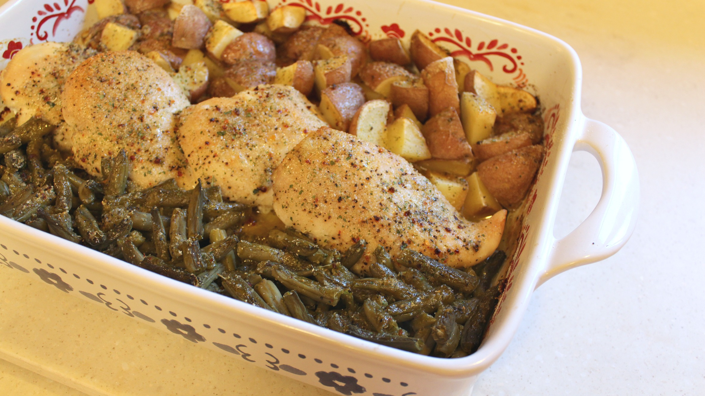 chicken in a baking dish with potatoes and green beans