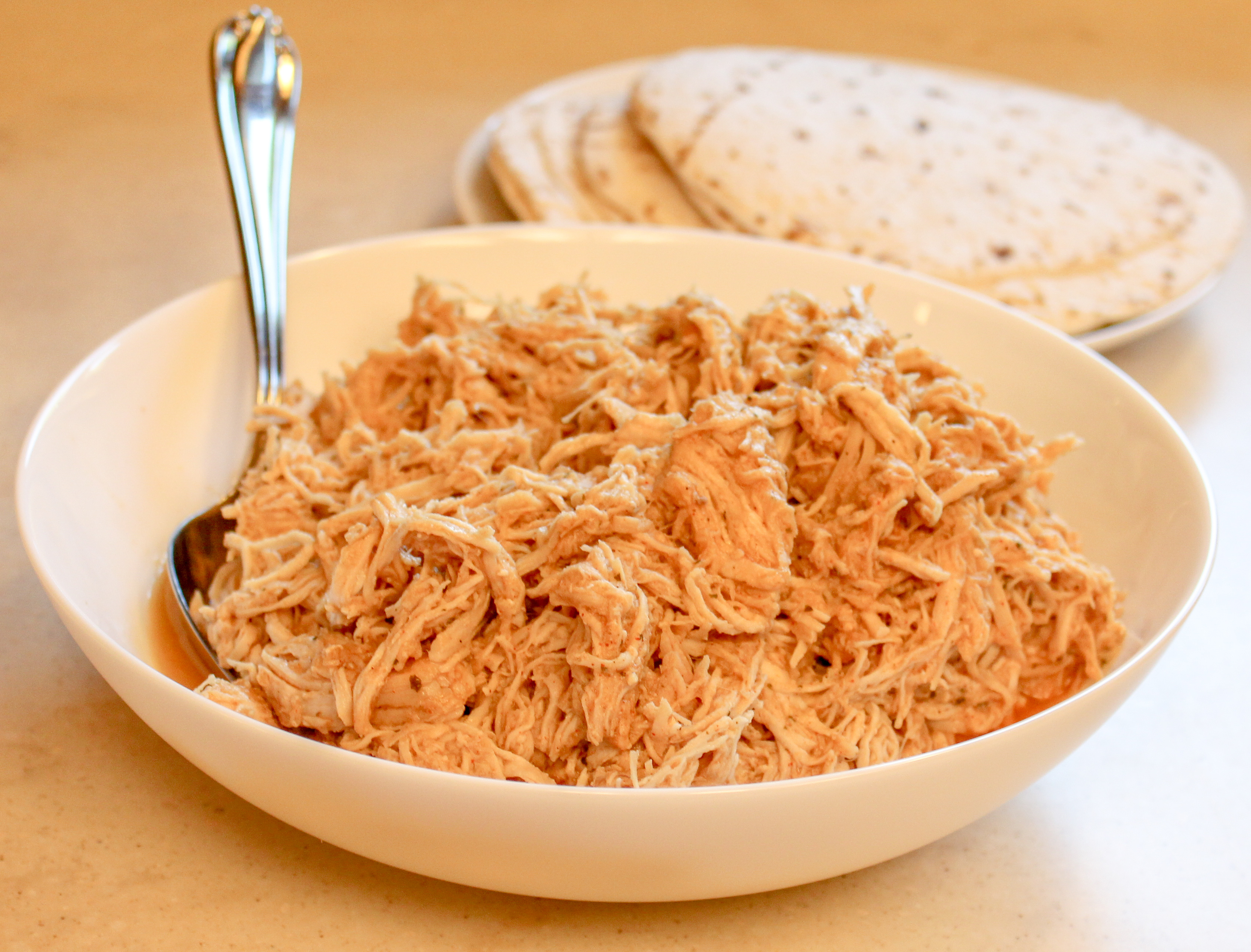 shredded chicken in a white bowl with a plate or tortillas in the background