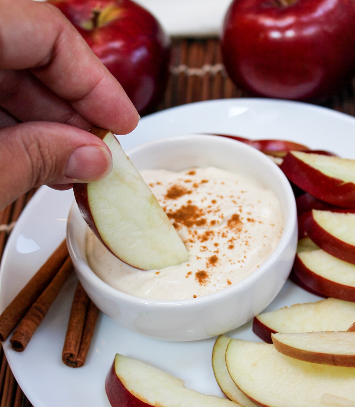 apple cider dip in a bowl with sliced apples and an apple dipped into the dip