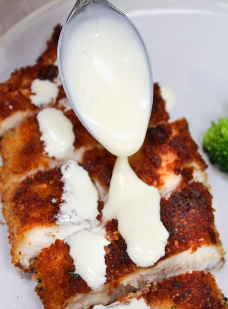 sauce spooned over Crispy Parmesan Chicken with Lemon Hollandaise