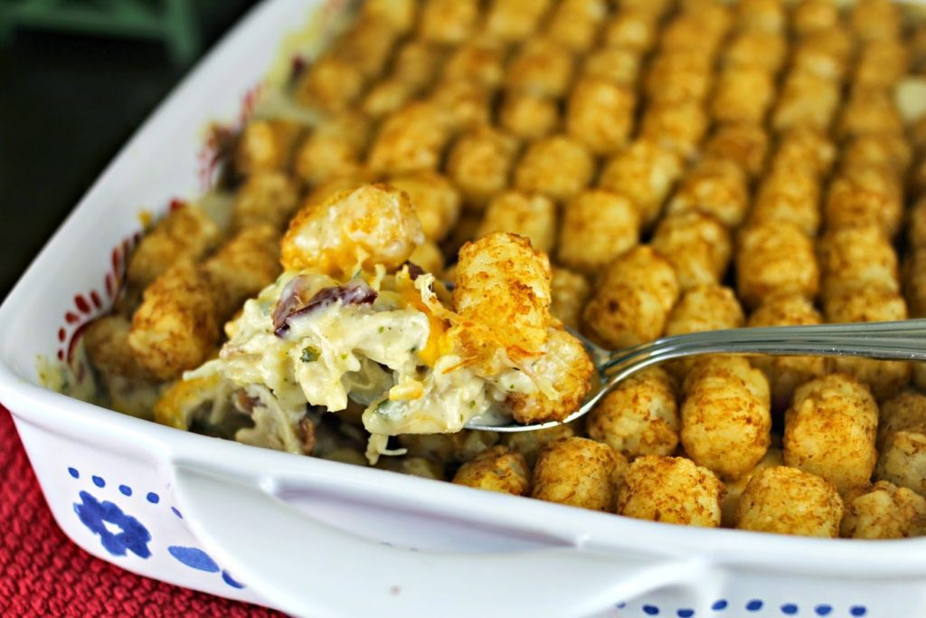A scoop from a casserole dish of chicken topped with tater tots
