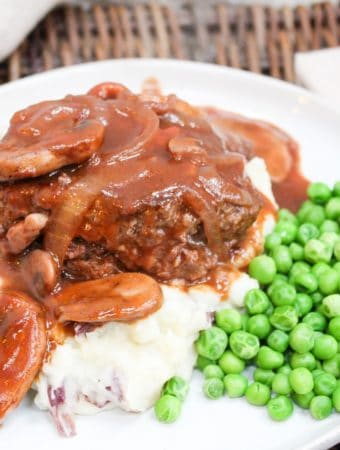 Salisbury steak on a plate with potatoes and peas