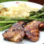 two grilled chicken thighs on a plate with grilled vegeetables