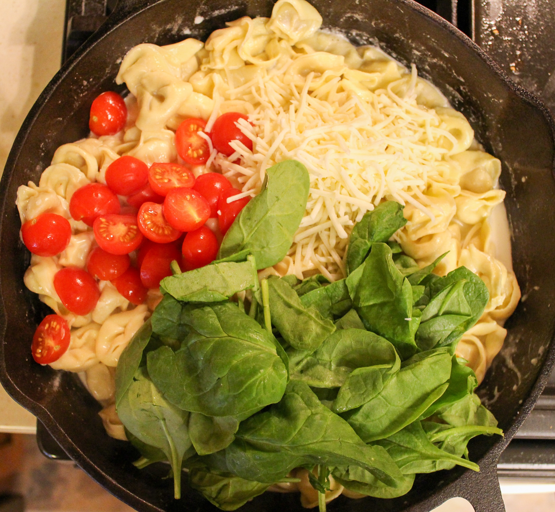 pasta in skillet with cheese, tomatoes, and spinach