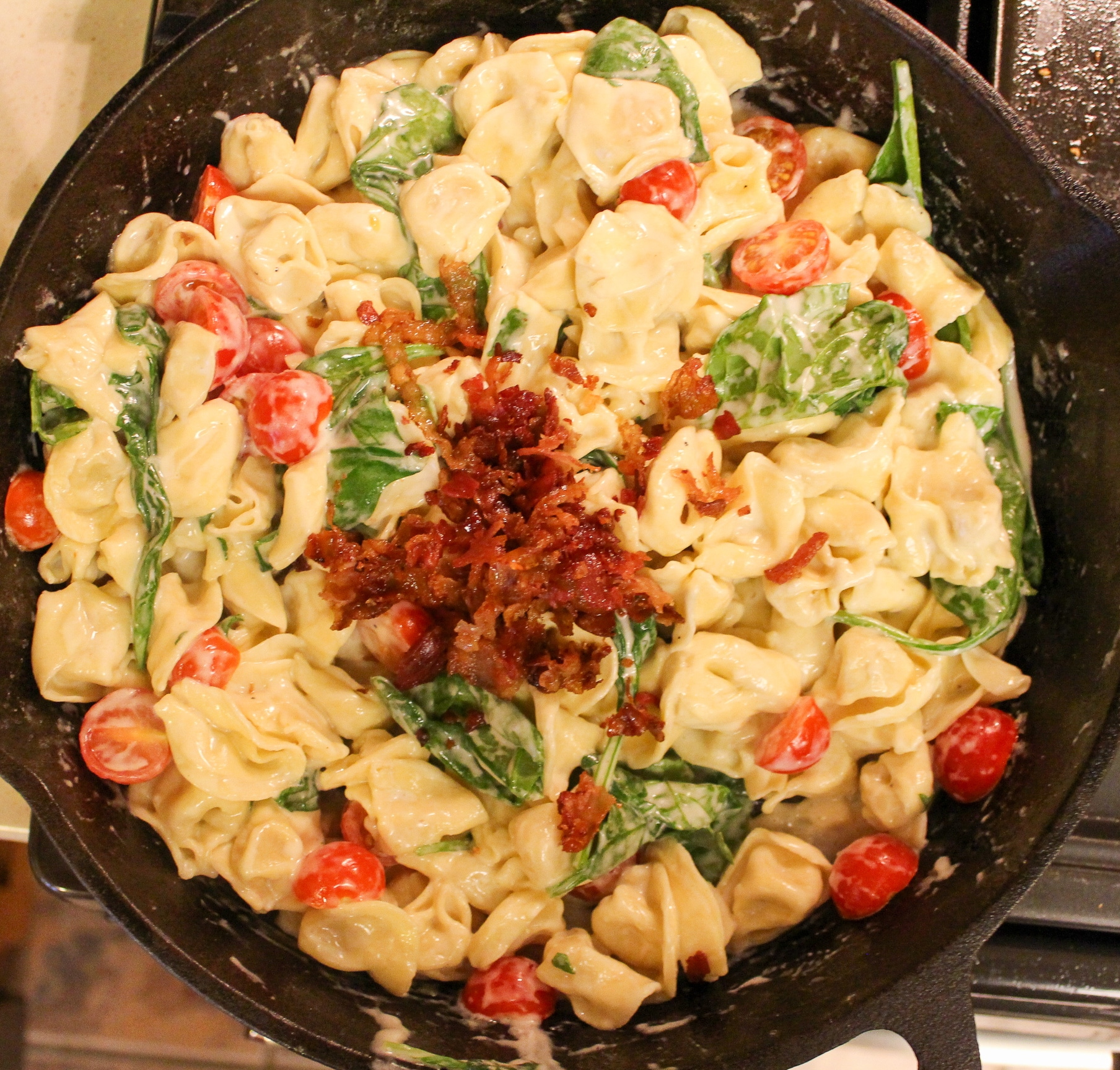pasta in skillet with cheese, tomatoes, and spinach with cooked chopped bacon on top