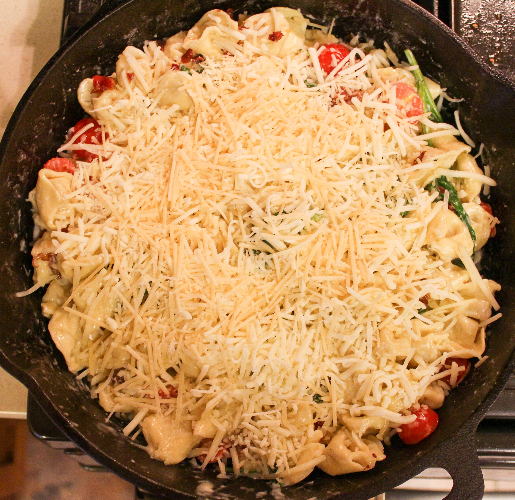 pasta in skillet with cheese, tomatoes, and spinach with cooked chopped bacon on top and cheese on top