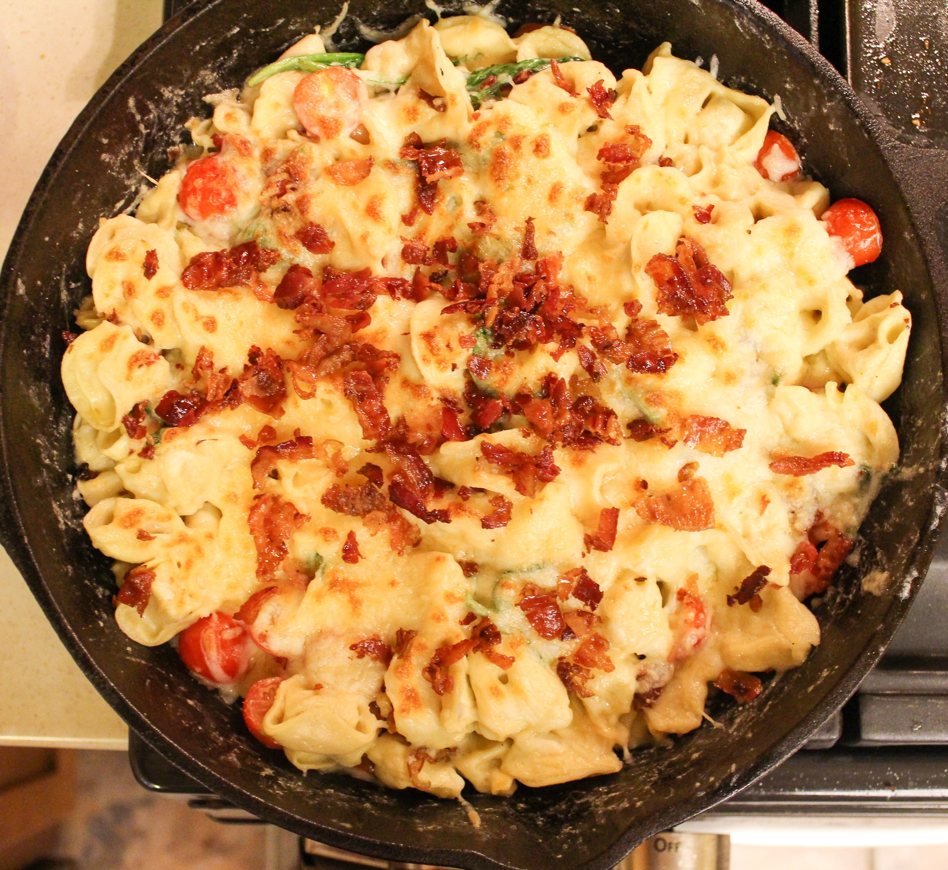 pasta in skillet topped with bacon