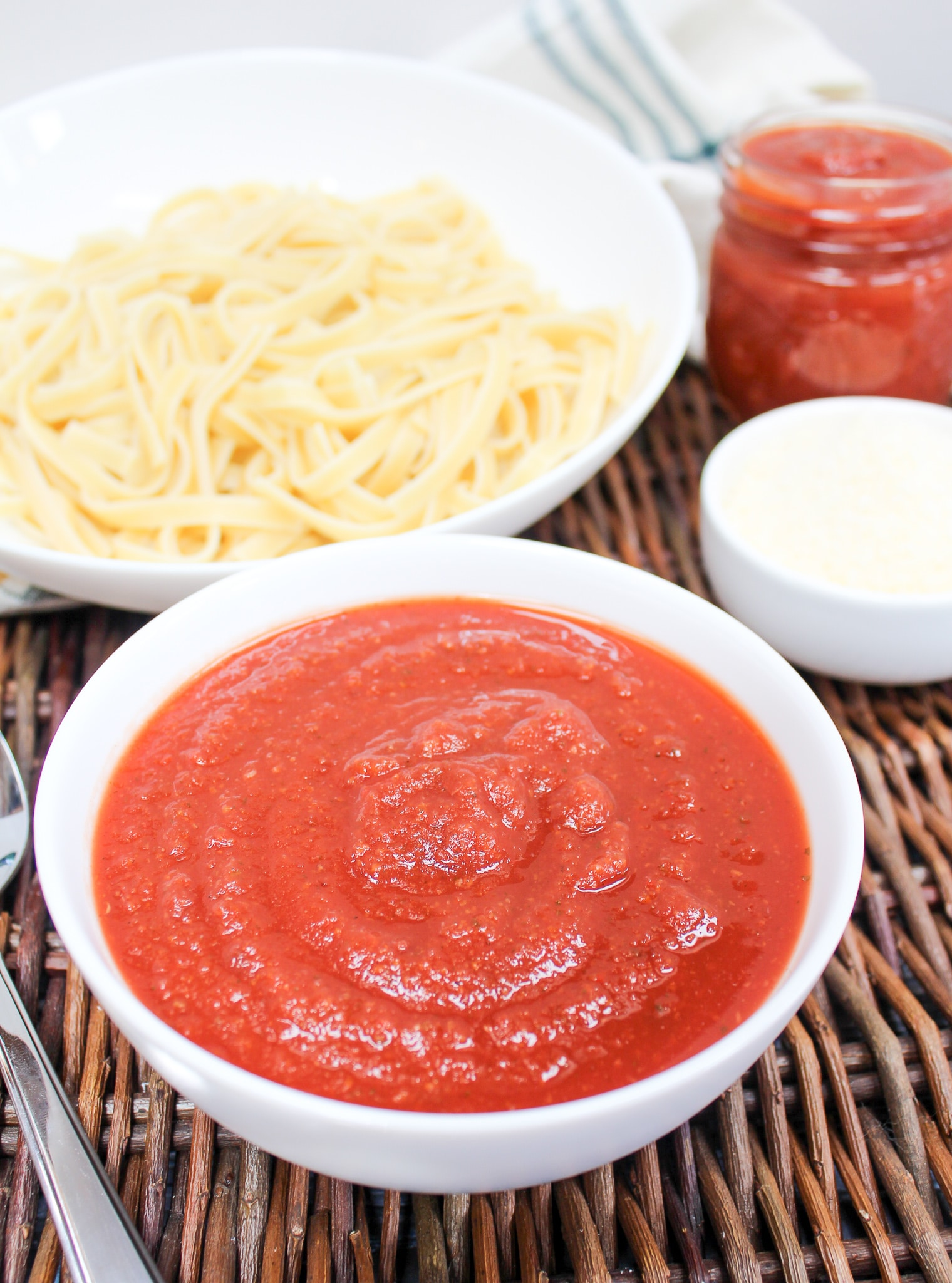 marinara sauce in a bowl with pasta in the background