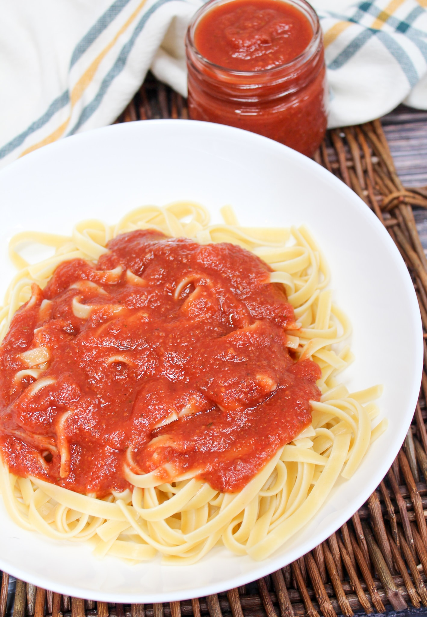 pasta sauce spooned over cooked pasta