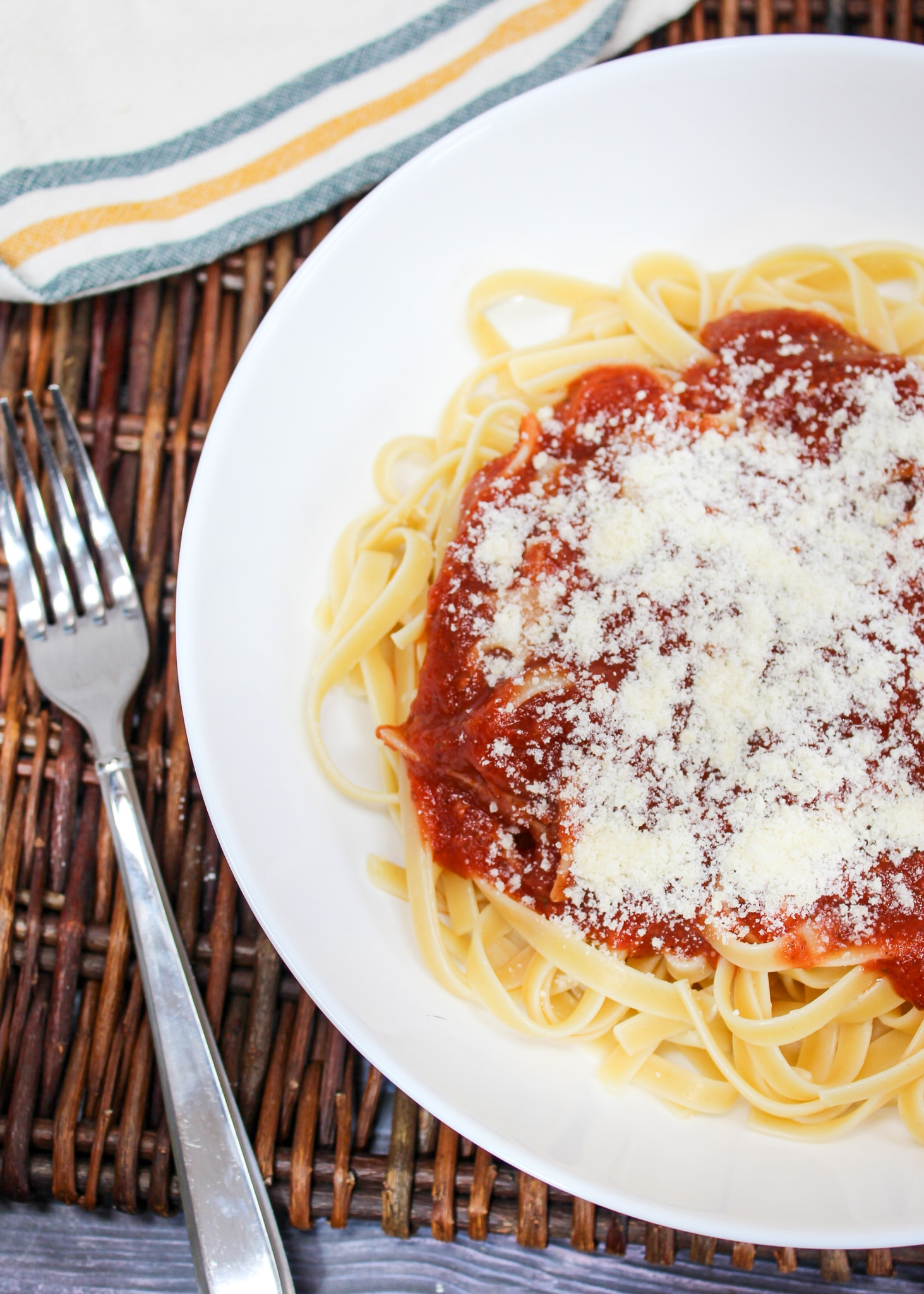 pasta sauce spooned over cooked pasta with parmesan cheese