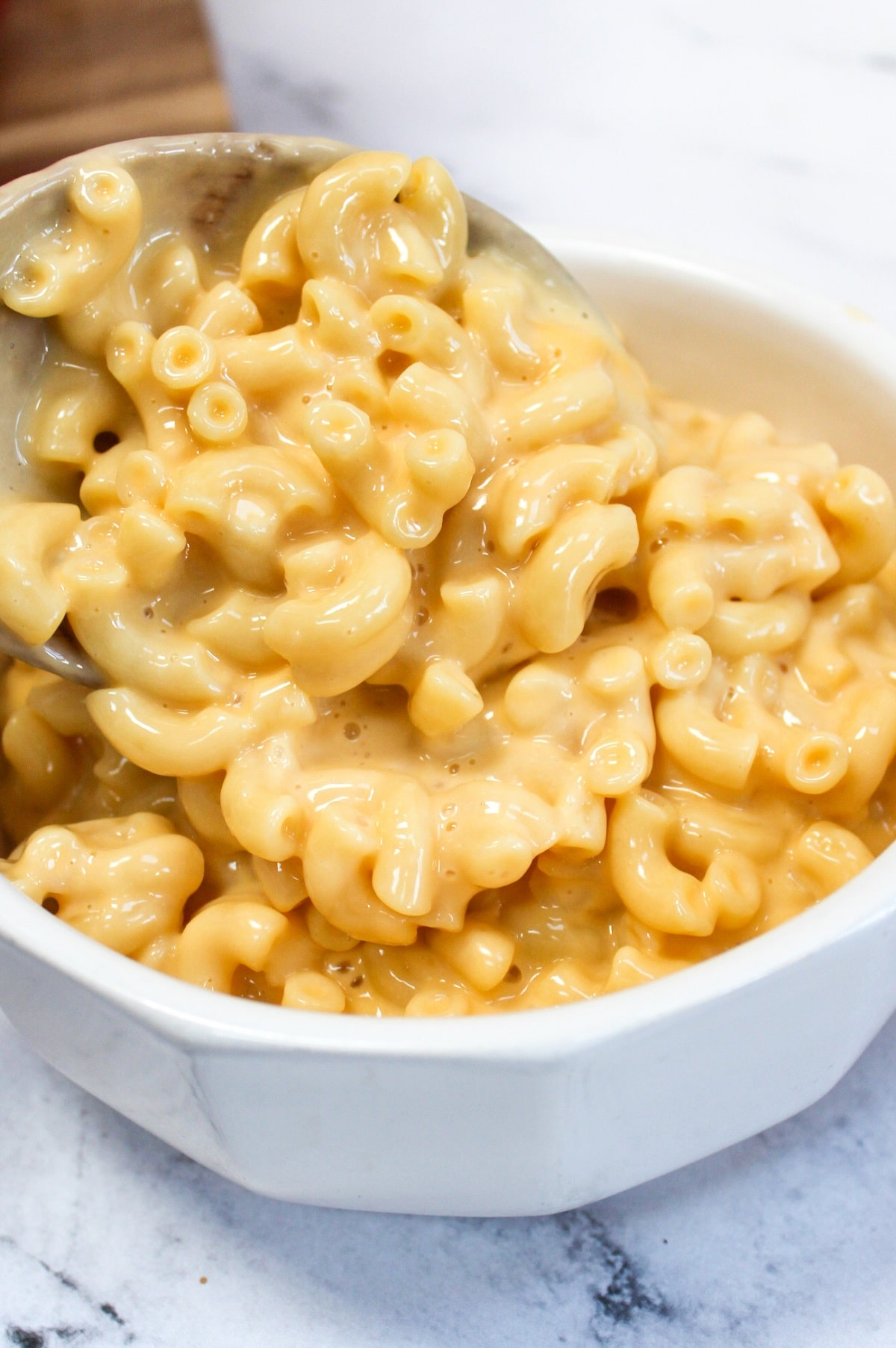 one-pot stove top mac and cheese put into a white bowl from a wooden spoon
