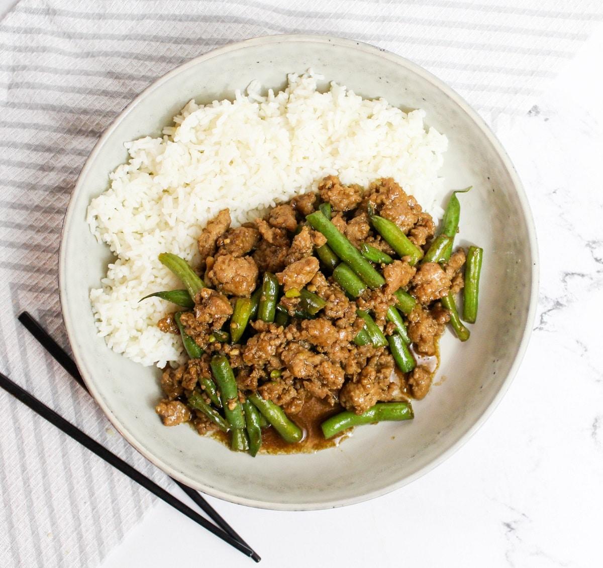 overhead photo Szechuan Green Beans and Ground Pork with chopsticks