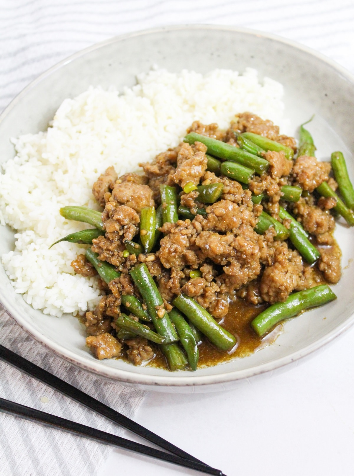 Szechuan Green Beans and Ground Pork in a white bowl with rice