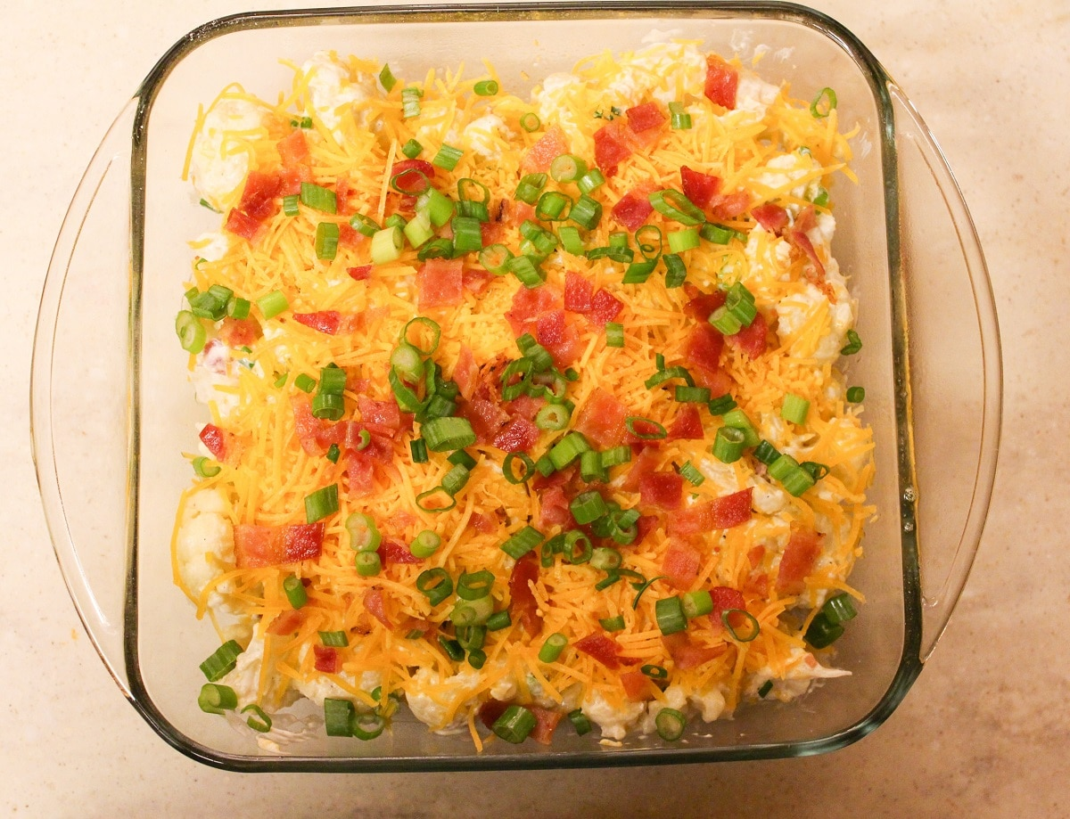 Casserole in a glass baking dish with bacon and onion