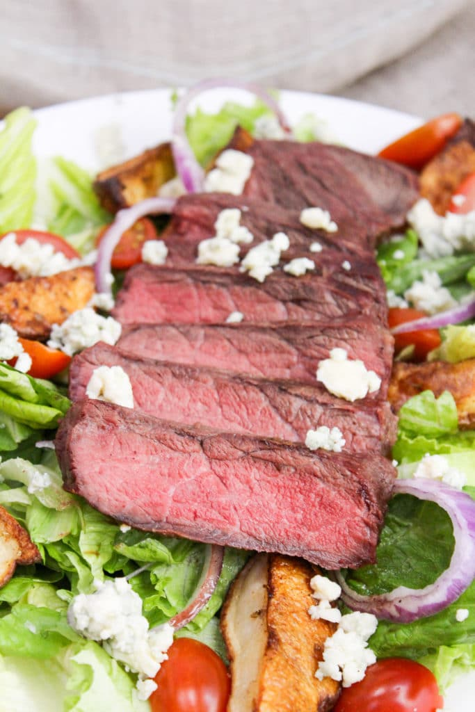 sliced steak on a salad