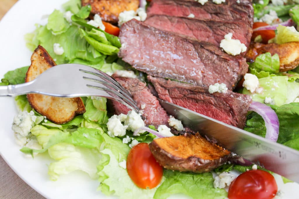 cutting the steak on a salad