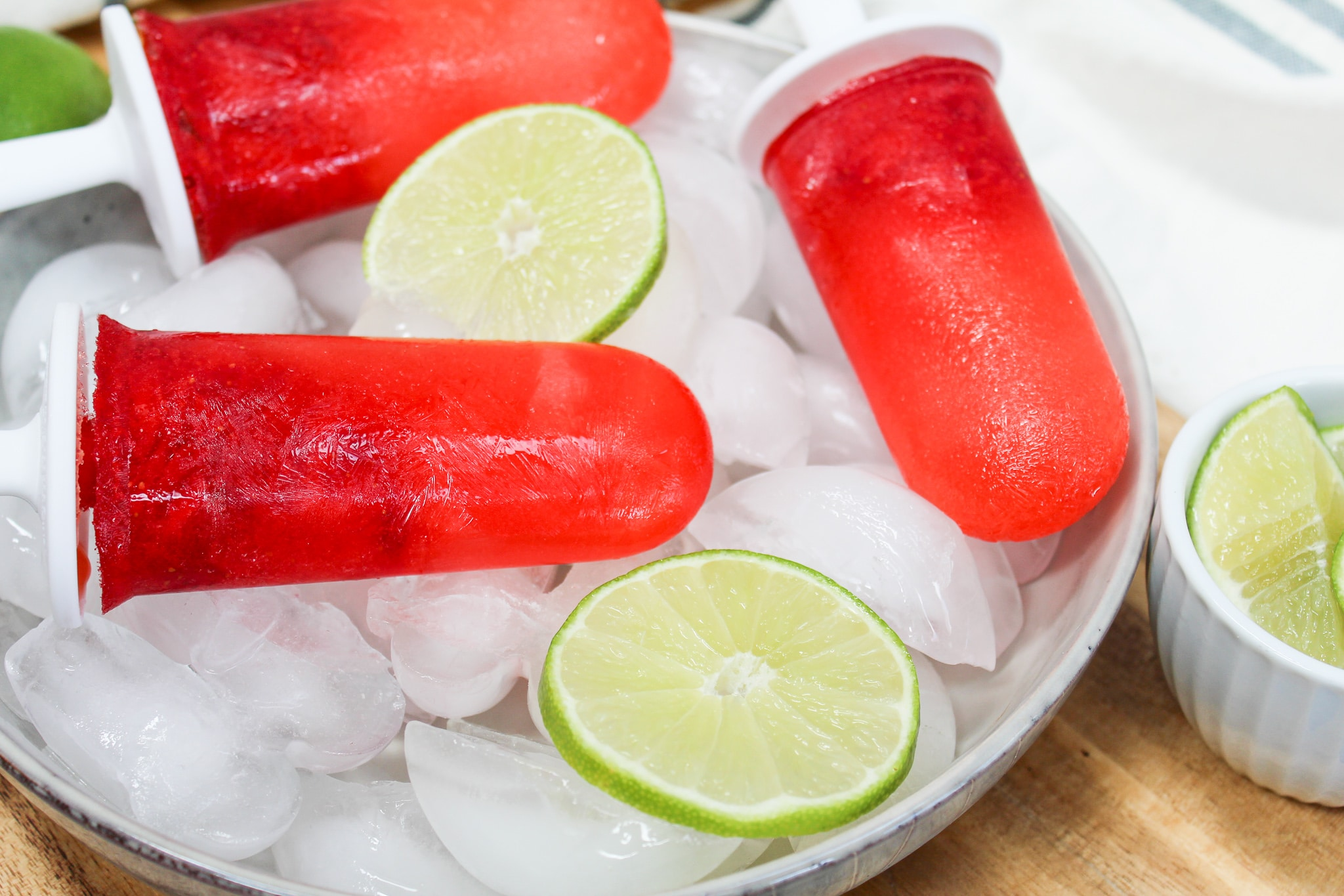 Strawberry Margarita Popsicle over ice with limes