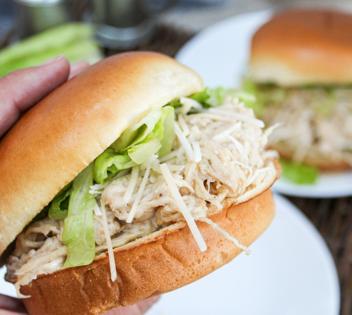 chicken on a bun with lettuce and cheese held in hand