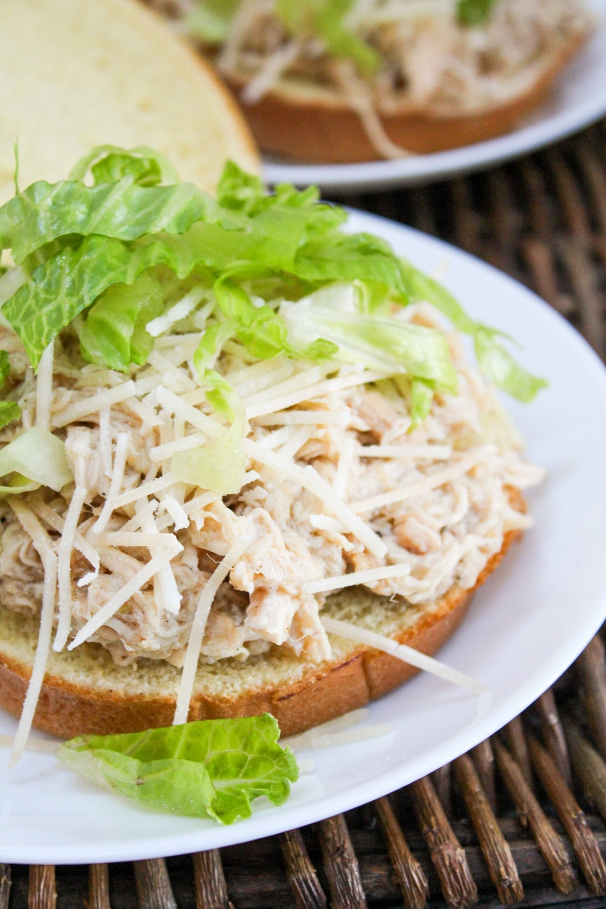plated chicken on a bun with lettuce and cheese