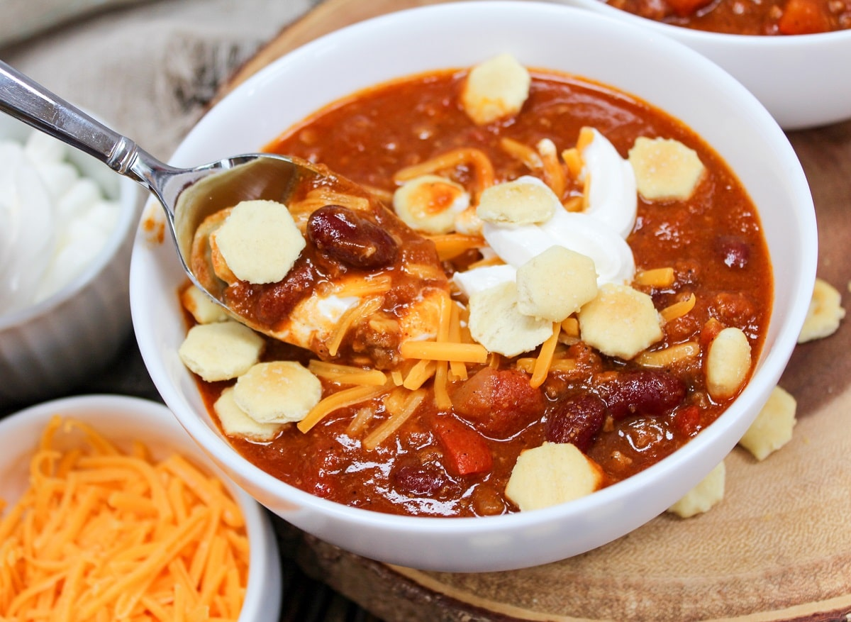 chili on a spoon with sour cream, cheese, and crackers