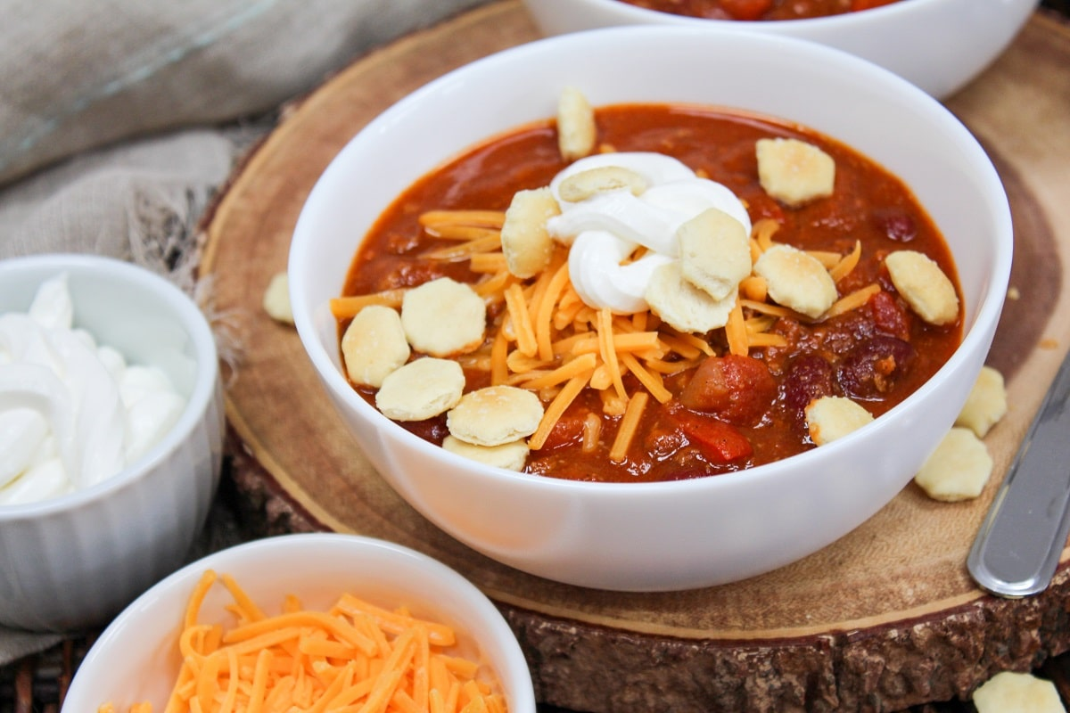 pumpkin chili in bowls with sour cream, cheese, and crackers
