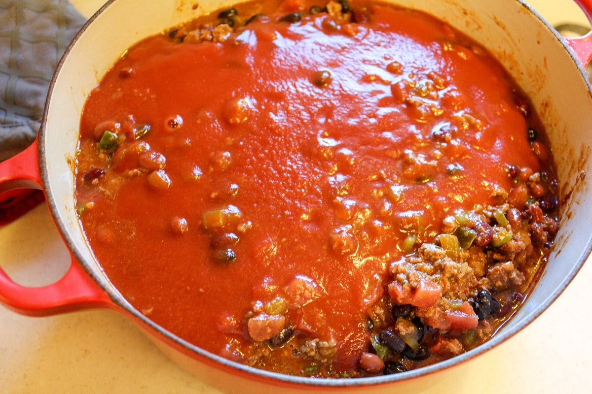 chili preparation in a pot with tomato sauce
