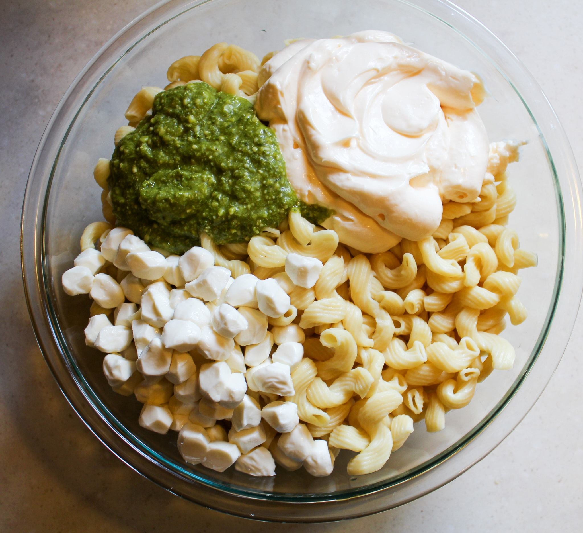 bowl of plain noodles with mayo, pesto, and cheese