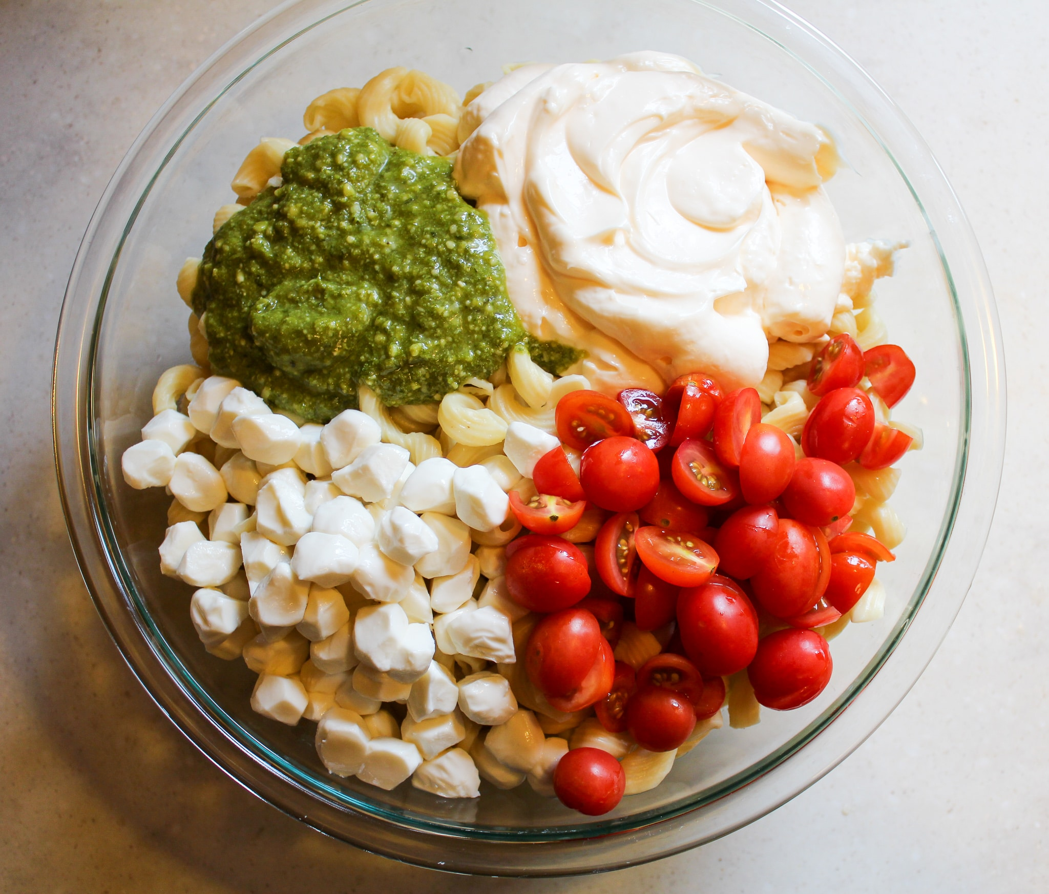 bowl of plain noodles with mayo, pesto, cheese, and tomatoes