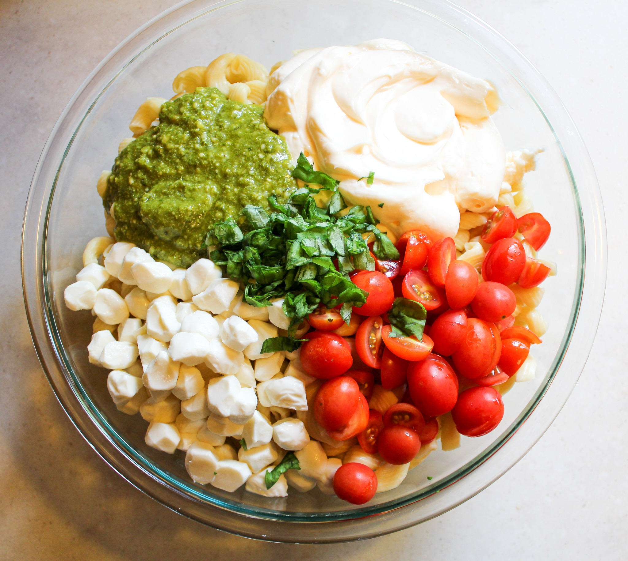 bowl of plain noodles with mayo, pesto, cheese, tomatoes, and basil