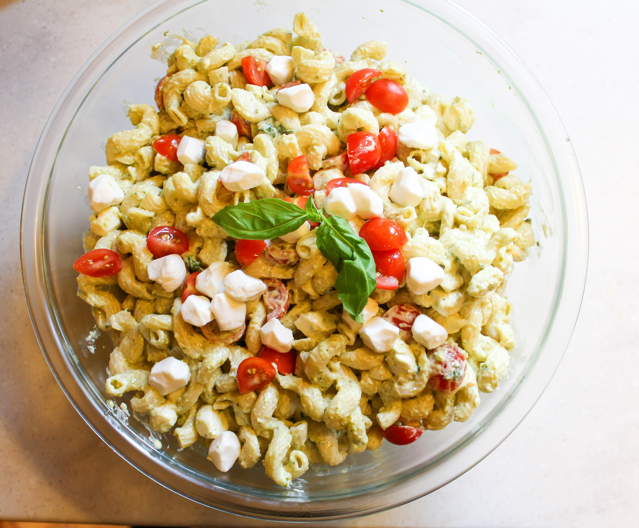 bowl of plain noodles with mayo, pesto, cheese, tomatoes, and basil mixed together with basil garnish