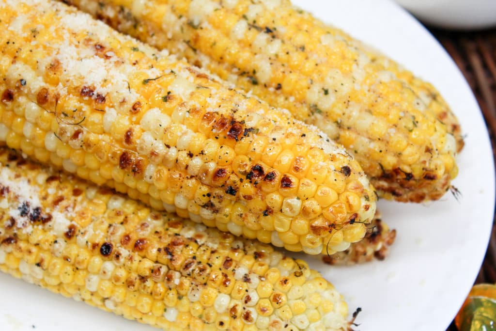grilled corn stacked on a plate