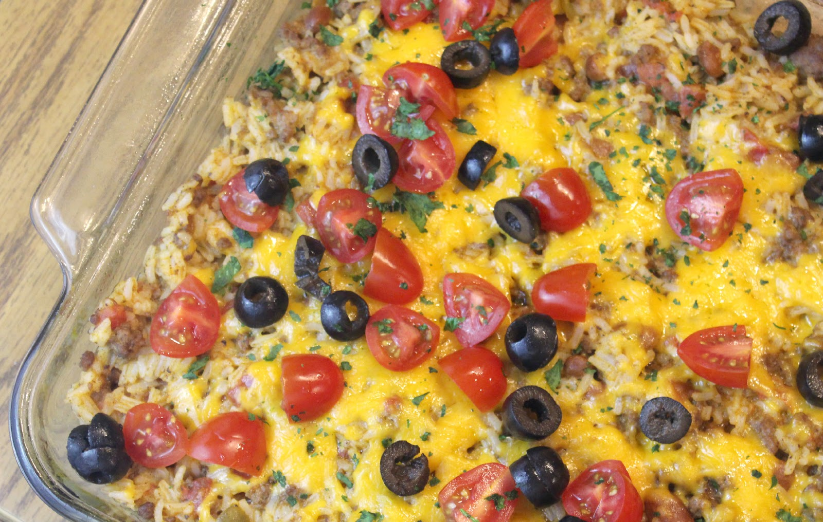 Cheese covered ground beef and rice. Topped with chopped tomatoes, sliced olives in a casserole dish