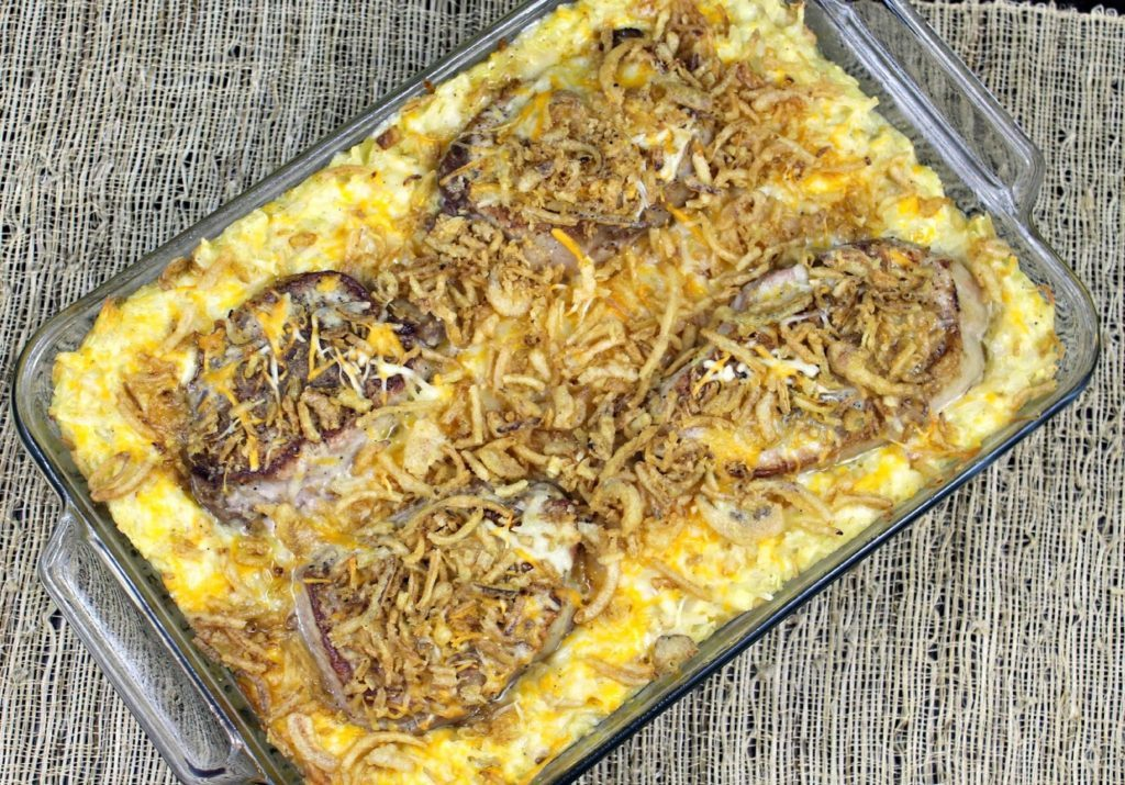 pork chops on top of cheesy potatoes in a casserole dish