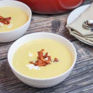 soup in white bowls topped with goast cheese crumbles and bacon