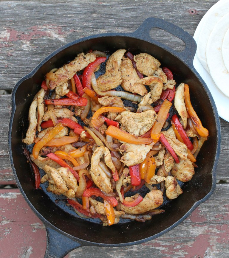 chicken peppers and onions in a cast iron pan