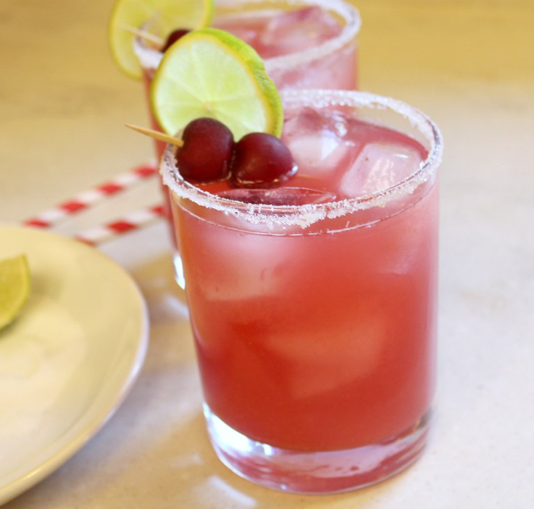 Red drink in a glass garnished with cherries and a lime slice