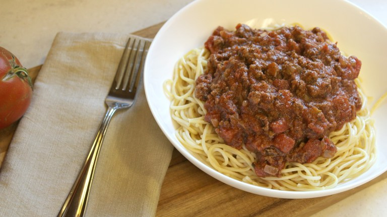 meat sauce and pasta on a white plate