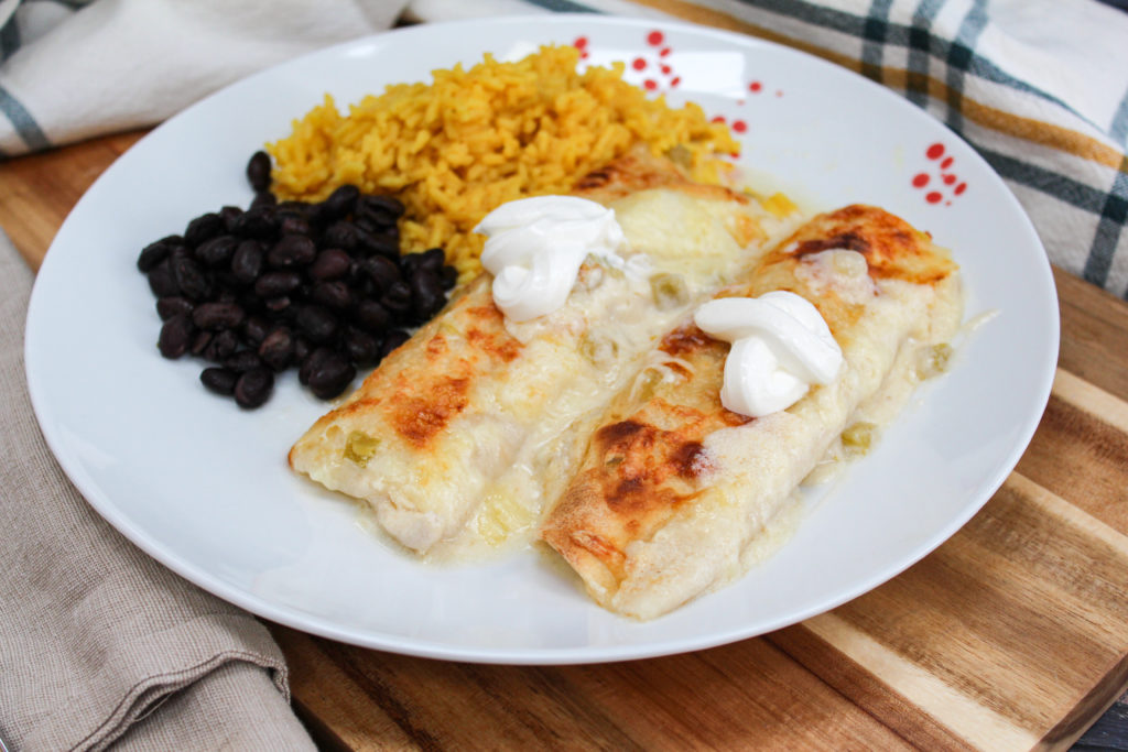 Chicken enchiladas on a plate with rice and beans
