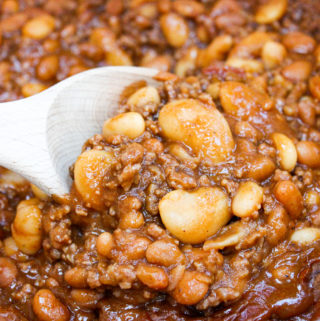 Baked beans in a pot with a wooden spoon
