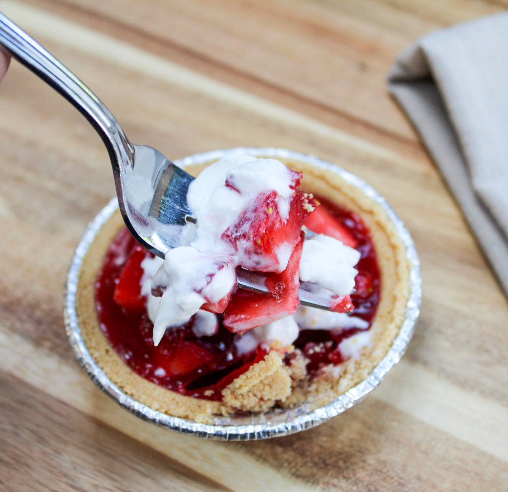 mini strawberry pies on a platter with whipped cream being eaten