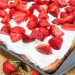 uncut photo of cake with whipped cream and strawberries