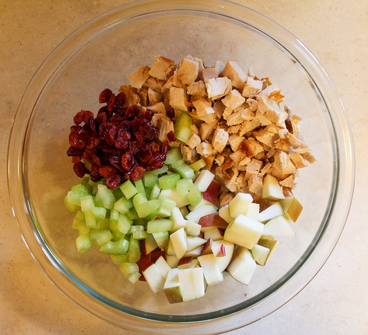 chopped turkey, celery, cranberry, and apple in a bowl