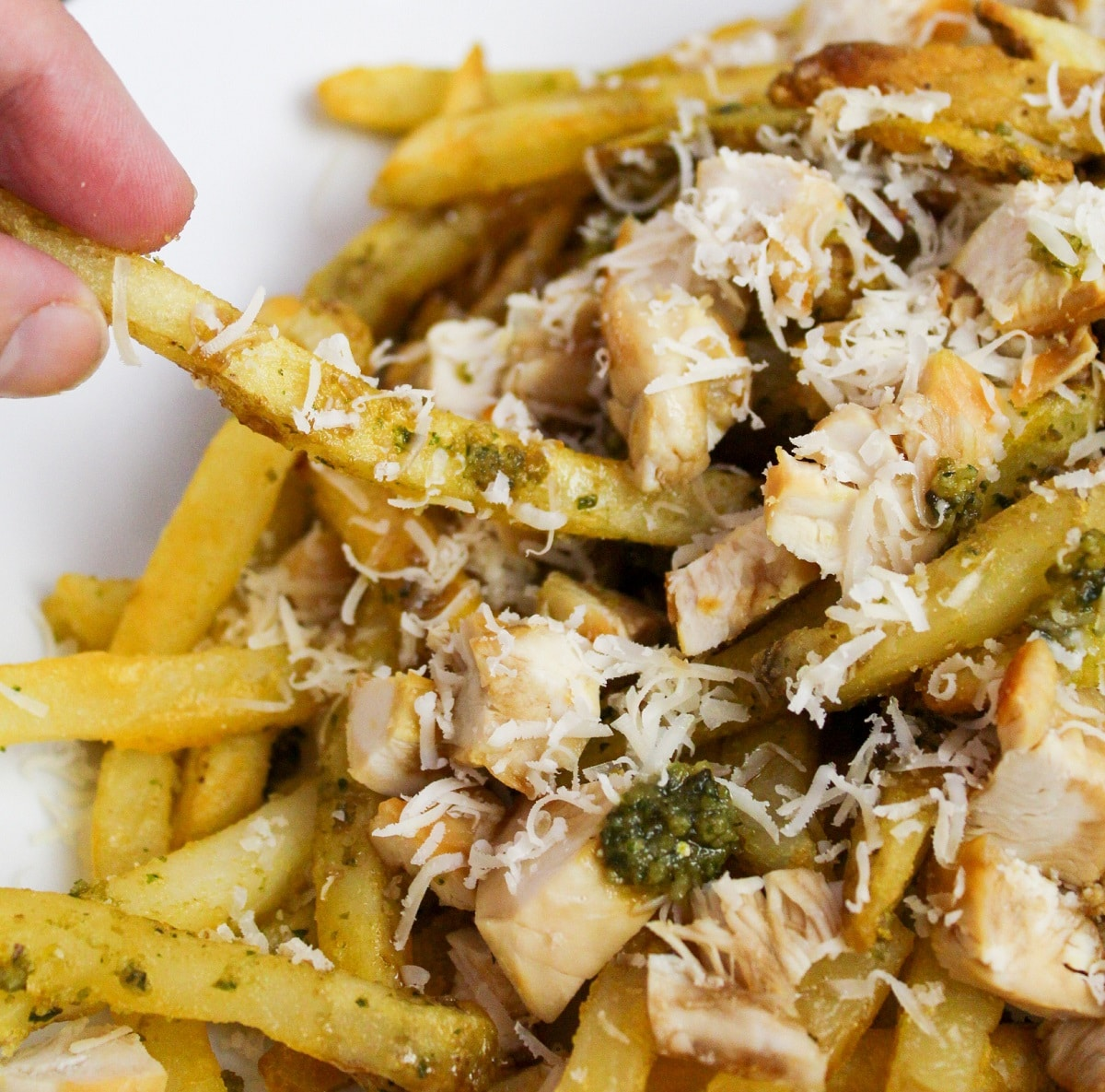 Pesto Chicken Fries with hand grabbing a fry